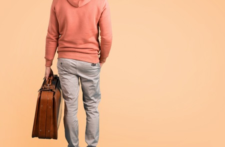 Man in a pink sweatshirt holding a vintage briefcase while walking on ocher background Stock Photo