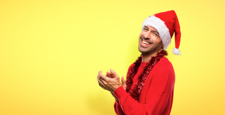Man with red clothes celebrating the Christmas holidays applauding after presentation in a conference on yellow background Stock Photo