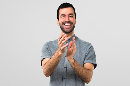 Handsome man applauding on grey background