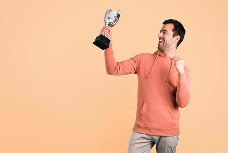 Man in a pink sweatshirt holding a trophy on ocher background