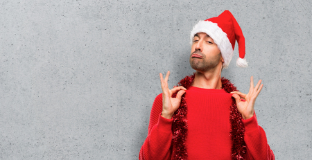 Man with red clothes celebrating the Christmas holidays proud and self-satisfied in love yourself concept on textured background Stock Photo