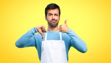 Man wearing an apron making good-bad sign. Undecided person between yes or not on yellow background