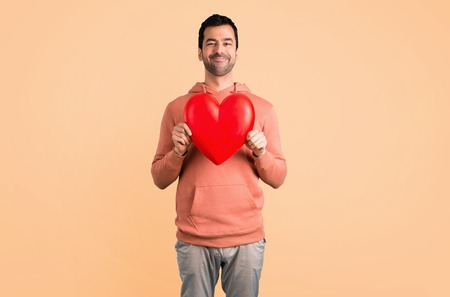Man in a pink sweatshirt holding a big heart icon toy on ocher background