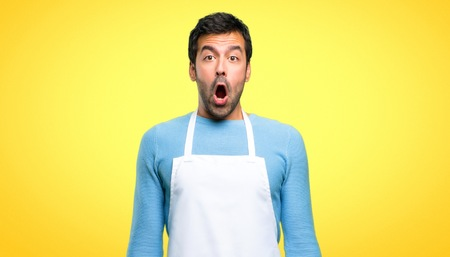 Man wearing an apron with surprise and shocked facial expression. Gaping because have just surprised with a gift on yellow background