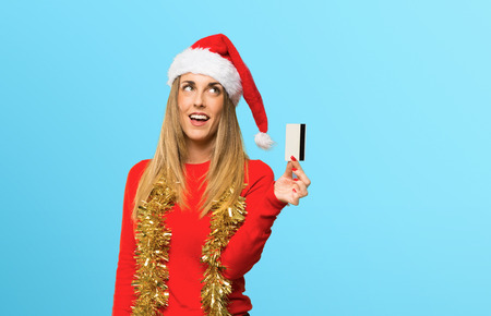 Blonde woman dressed up for christmas holidays holding a credit card and thinking on blue background