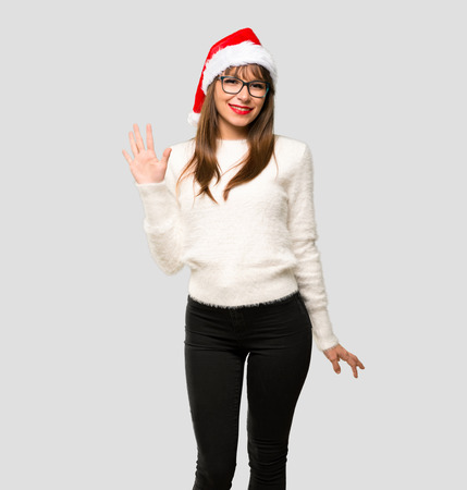 Girl with celebrating the christmas holidays counting five with fingers on isolated grey background Stock Photo
