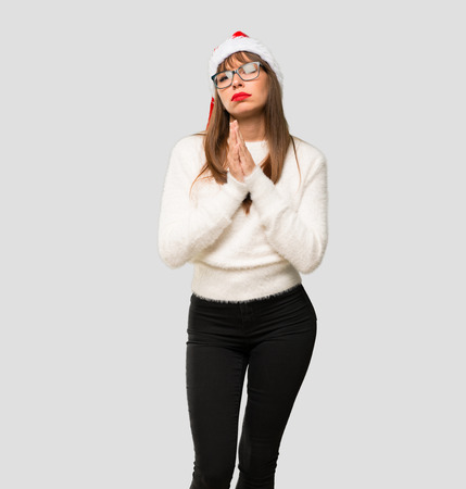 Girl with celebrating the christmas holidays keeps palm together. Person asks for something on isolated grey background