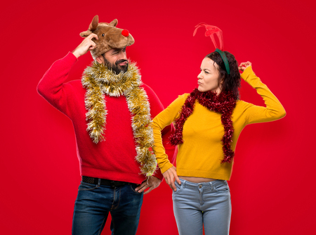 Couple dressed up for the christmas holidays having doubts and with confuse face while scratching head on isolated red background