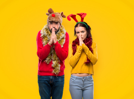 Couple dressed up for the christmas holidays keeps palm together. Person asks for something on yellow background