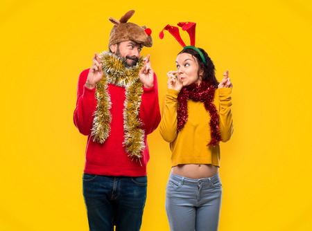Couple dressed up for the christmas holidays with fingers crossing and wishing the best on yellow background Reklamní fotografie