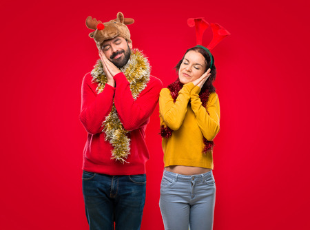 Couple dressed up for the christmas holidays making sleep gesture. Adorable sweet expression on isolated red background Banco de Imagens