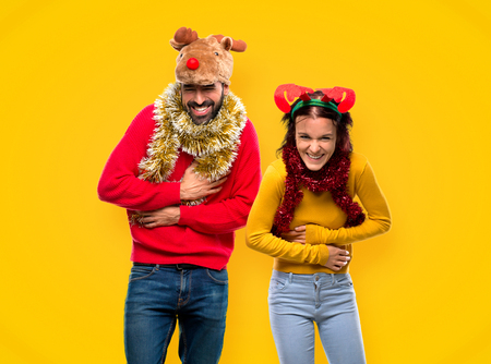 Couple dressed up for the christmas holidays smiling a lot while putting hands on chest on yellow background