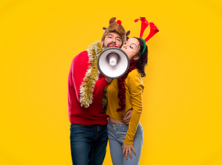 Couple dressed up for the christmas holidays holding a megaphone on yellow background