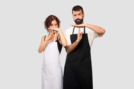 Couple of cooks making stop gesture with her hand to stop an act on grey background