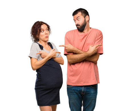 Couple with pregnant woman pointing to the laterals having doubts. Undecided person on isolated white background