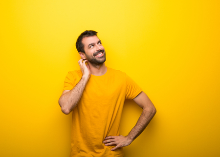 Man on isolated vibrant yellow color thinking an idea while scratching head Imagens