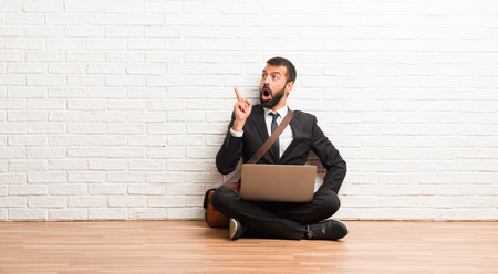 Businessman with his laptop sitting on the floor standing and thinking an idea pointing the finger up
