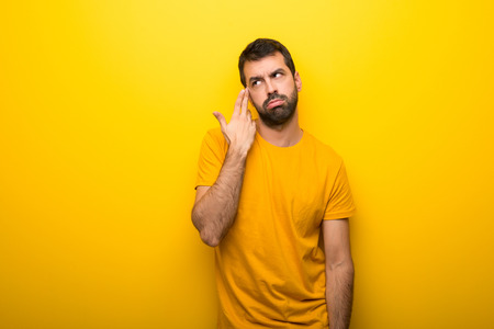 Man on isolated vibrant yellow color with problems making suicide gesture