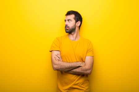 Man on isolated vibrant yellow color with confuse face expression while bites lip