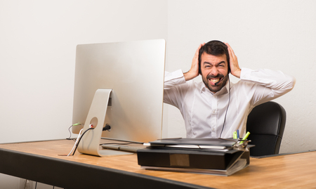 Telemarketer man in a office covering both ears with hands