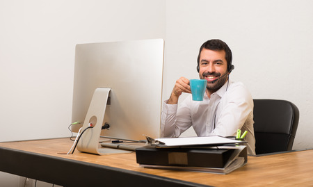 Telemarketer man in a office holding a cup of coffee 版權商用圖片