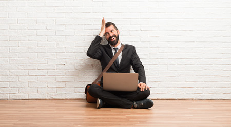 Businessman with his laptop sitting on the floor has just realized something and has intending the solution