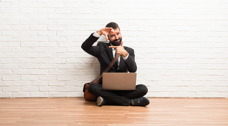 Businessman with his laptop sitting on the floor focusing face. Framing symbol