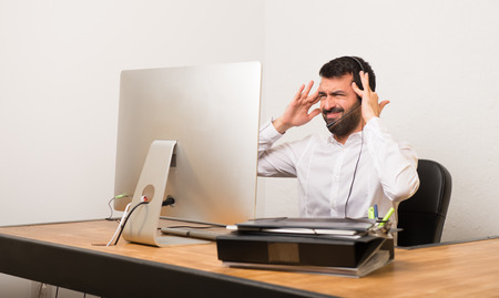 Telemarketer man in a office unhappy and frustrated with something