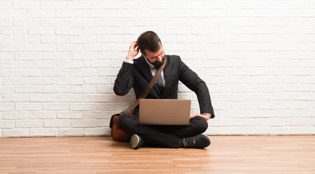 Businessman with his laptop sitting on the floor on back position looking back while scratching head
