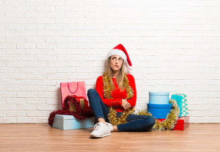 Girl with christmas hat and many gifts celebrating the christmas holidays having doubts and with confuse face expression Stock Photo