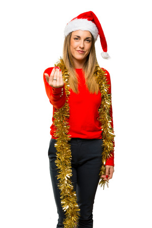 Blonde woman dressed up for christmas holidays presenting and inviting to come with hand on isolated white background