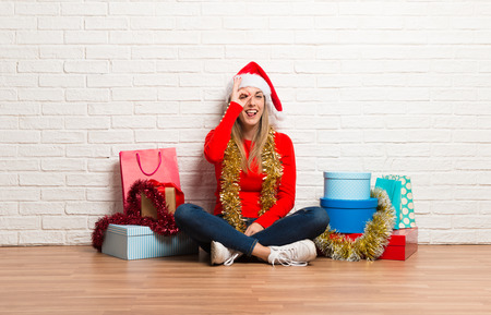 Girl with christmas hat and many gifts celebrating the christmas holidays makes funny and crazy face emotion