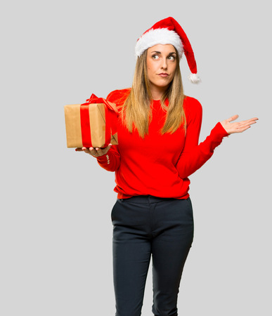Blonde woman dressed up for christmas holidays having doubts and with confuse face expression on isolated grey background Stockfoto