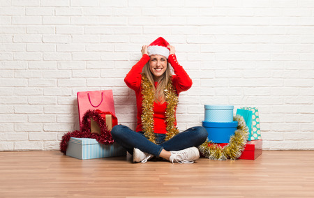 Girl with christmas hat and many gifts celebrating the christmas holidays unhappy and frustrated with something. Negative facial expression