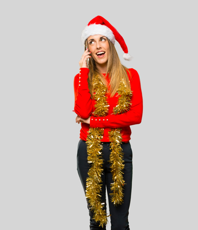 Blonde woman dressed up for christmas holidays keeping a conversation with the mobile phone with someone on isolated grey background