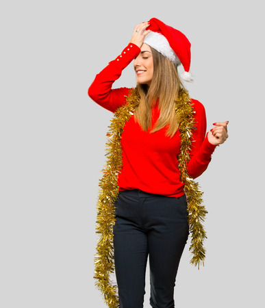 Blonde woman dressed up for christmas holidays has just realized something and has intending the solution on isolated grey background