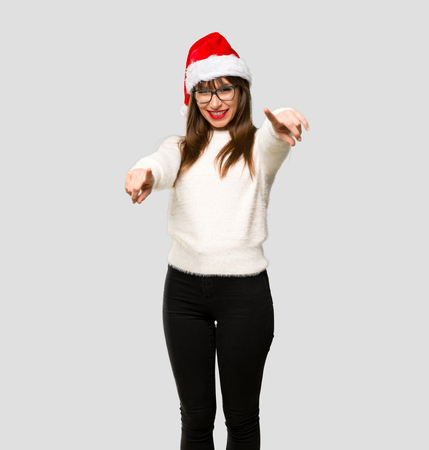 Girl with celebrating the christmas holidays points finger at you while smiling on isolated grey background