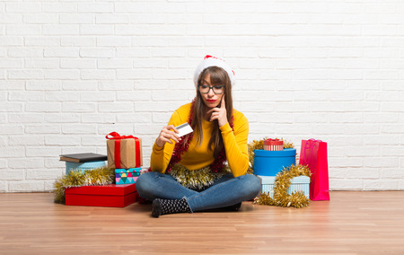 Girl celebrating the christmas holidays holding a credit card and surprised