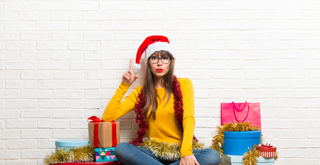 Girl celebrating the christmas holidays standing and thinking an idea Stock Photo