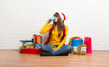 Girl celebrating the christmas holidays drinking hot coffee in takeaway paper cup