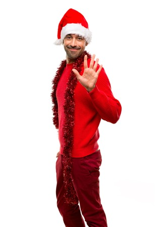 Man with red clothes celebrating the Christmas holidays counting five with fingers on isolated white background