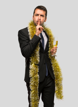 Man with champagne celebrating new year 2019 showing a sign of silence gesture putting finger in mouth on isolated grey background