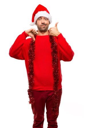 Man with red clothes celebrating the Christmas holidays making good-bad sign. Undecided between yes or not on isolated white background Stock Photo