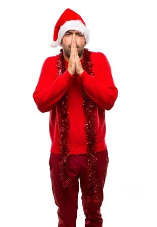 Man with red clothes celebrating the Christmas holidays keeps palm together. Person asks for something on isolated white background Zdjęcie Seryjne