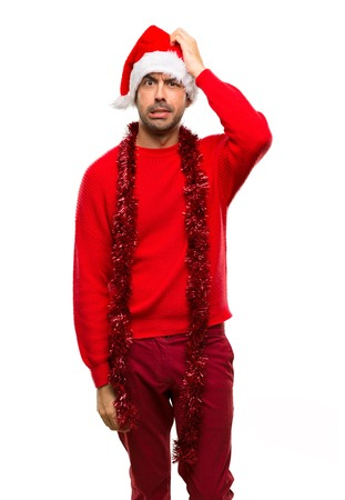 Man with red clothes celebrating the Christmas holidays with an expression of frustration and not understanding on isolated white background