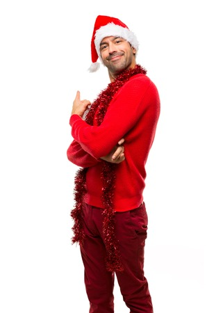 Man with red clothes celebrating the Christmas holidays pointing back with the index finger on isolated white background