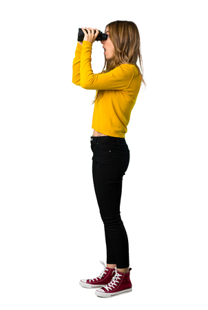 A full-length shot of a young girl with yellow sweater and looking in the distance with binoculars on isolated white background