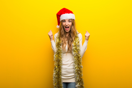 Girl celebrating the christmas holidays on yellow background celebrating a victory in winner position Stock Photo