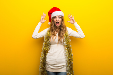 Girl celebrating the christmas holidays on yellow background with surprise and shocked facial expression