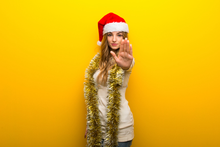 Girl celebrating the christmas holidays on yellow background making stop gesture denying a situation that thinks wrong